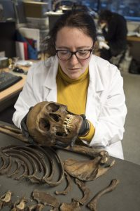 Human Osteologist Niamh Carty examines the booted man's skeleton (c) MOLA Headland Infrastructure