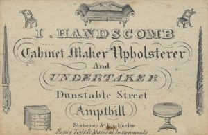 19th century advert for I. Handscomb whose business included Cabinet making, Upholstery and Undertaking. Note the inverted torches which were used to symbolise life extinguished.