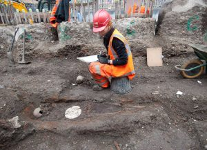 An archaeologist records a salt plate found in a burial during the excavation of Bedlam burial ground March 2015 © MOLA